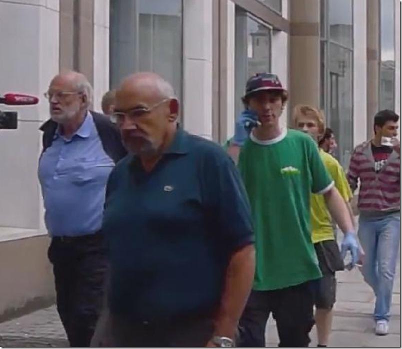 Caps, grønn t-skjorte, shorts, mobiltelefon og blå latexhansker