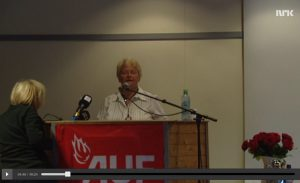 Gro Harlem Brundtland taler i storsalen i kafébygningen på Utøya den 22. juli 2011. Legg merke til TV2- og P4-mikrofonene, samt NRK-logoen i øvre høyre bildehjørne. Bildet er tatt ut av NRK-dokumentaren 22.07.22