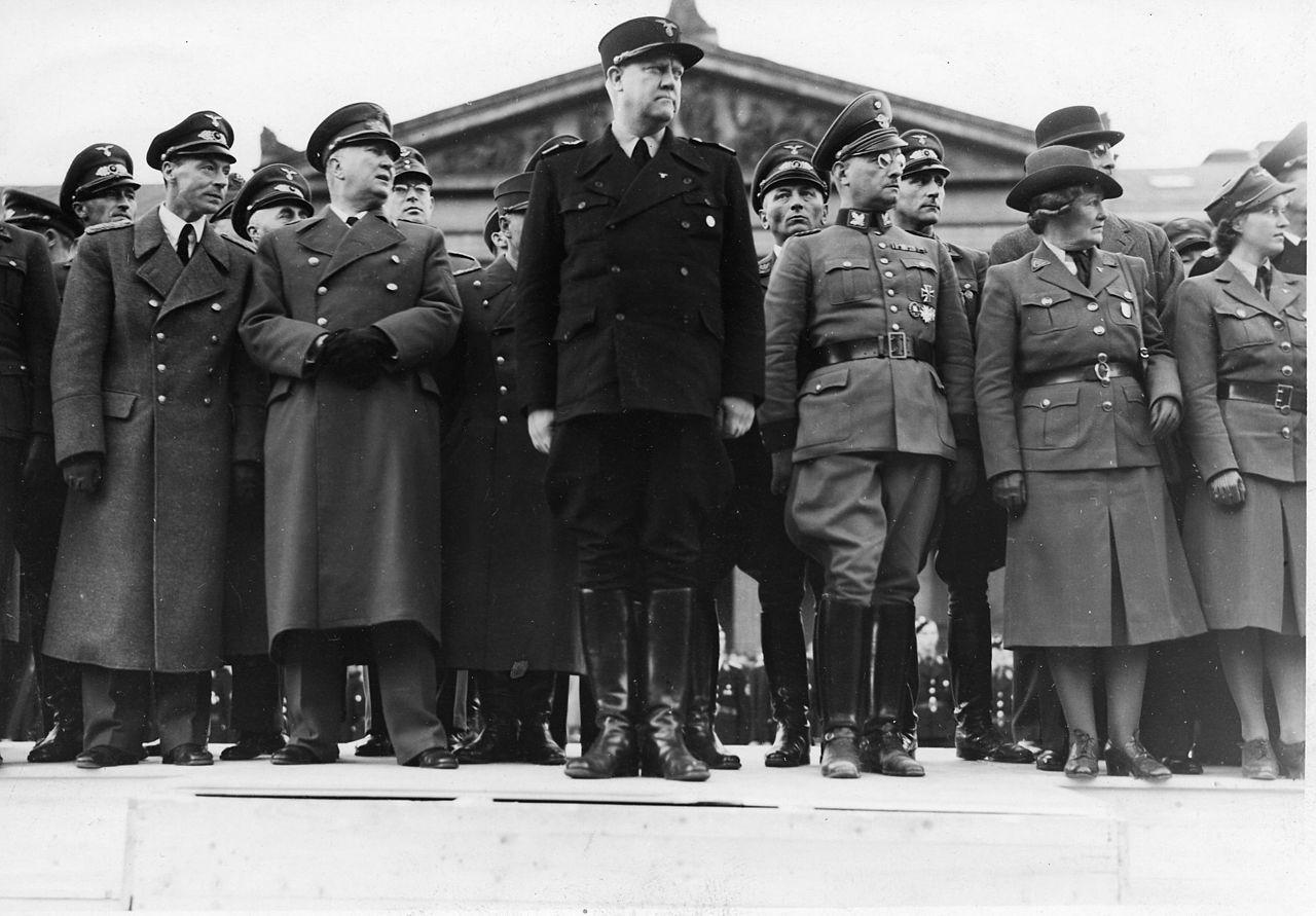 Hagelin (nummer to fra venstre) mellom minister Lunde og «Føreren» under NS' partilandsmøte i Oslo i 1942 (med kvinnehirdlederen Olga Bjoner nest ytterst til høyre). Hagelin var handels- og forsyningsminister i Quislings regjering. NS satte ham under intern etterforskning i 1943, på mistanke om korrupsjon, og anmodet ham om å søke avskjed i 1944, noe han gjorde. Hagelin ble etter krigen dømt og henrettet ved skyting 25. mai 1946 på Akershus festning. Foto: Riksarkivet